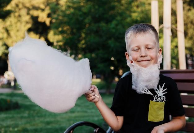 De gelukkige jonge jongen eet gesponnen suiker die van kleverige gesponnen suikerzitting wordt gemaakt op een bank in het park. gelukkige jongen maakte een baard van suikerspin.