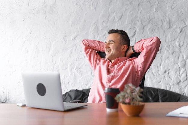 De gelukkige jonge mens bekijkt door het venster bij wotkplace