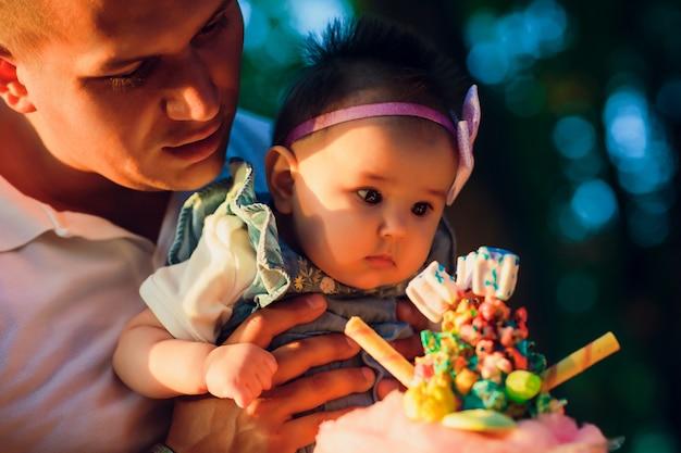 De gelukkige jonge mens die een glimlachende 2-4 maanden oudbaby houdt toont snoepjes