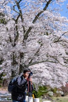 De gelukkige jonge mens die reizen neemt een foto met mooie roze cherry blossom