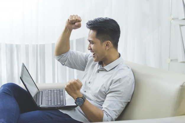 De gelukkige jonge mens heft zijn hand op. succes