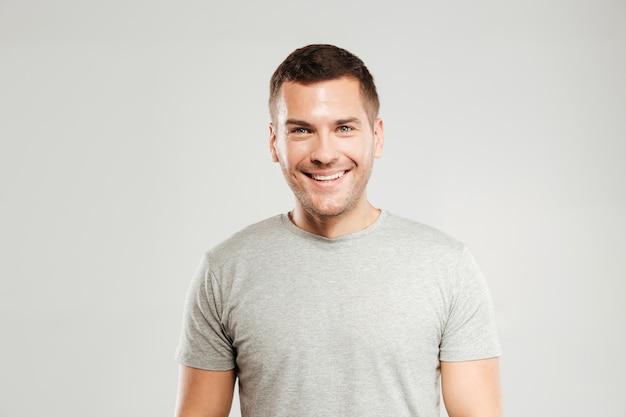 De gelukkige jonge mens kleedde zich in grijze geïsoleerde t-shirt