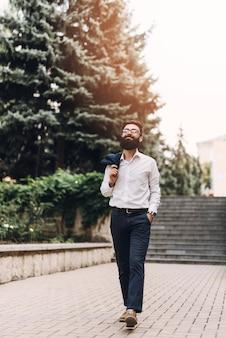 De gelukkige jonge mens met dient zijn zakken in lopend in het park