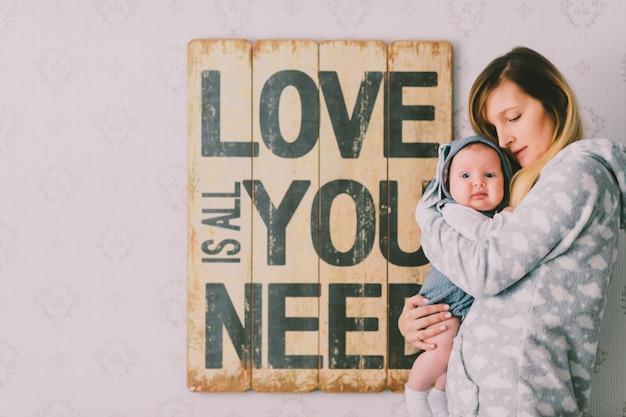 De gelukkige jonge moeder die haar zuigelingsbaby houden dient binnen ruimte in