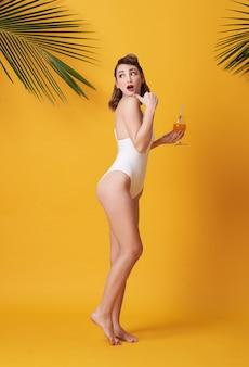 De gelukkige jonge mooie vrouw kleedde zich in badmode houdend een sinaasappel