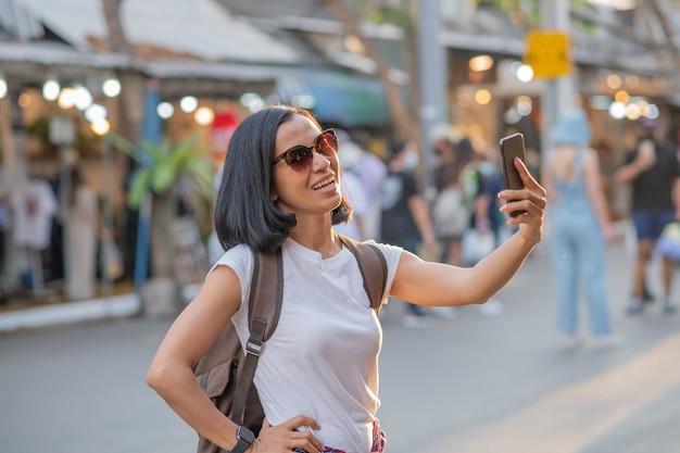 De gelukkige jonge reis aziatische vrouw die mobiele telefoon met behulp van en ontspant op straat.