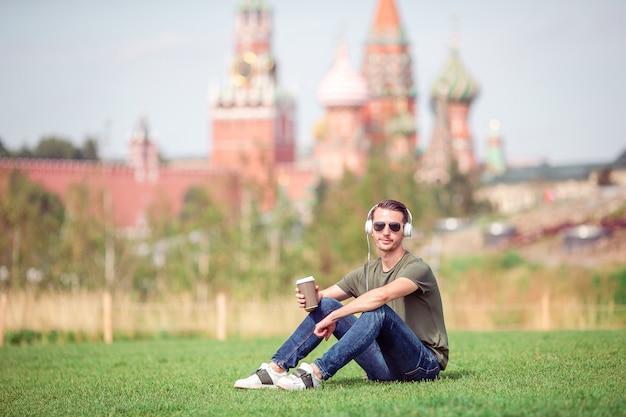 De gelukkige jonge stedelijke mens geniet van zijn onderbreking in de stad