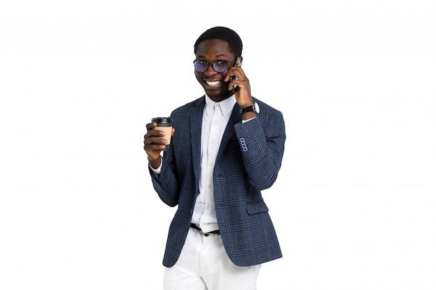 De gelukkige jonge succesvolle mens in bedrijfskleding drinkt meeneemkoffie en spreekt telefonisch
