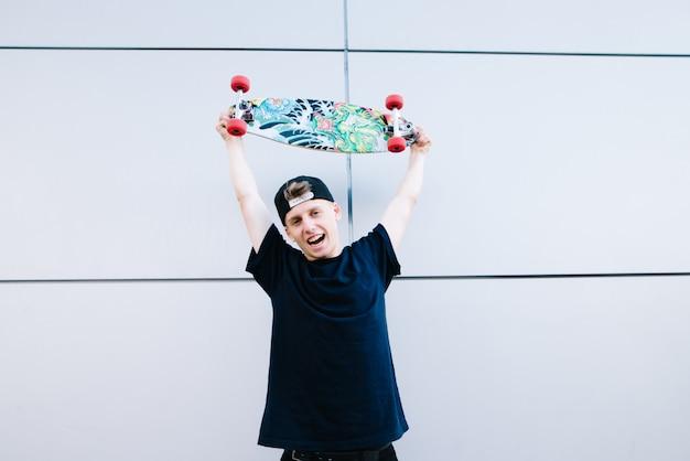 De gelukkige jonge tienerschaatser hief het bord over zijn hoofd op en verheugt zich. blije schaatser op een grijze achtergrond.