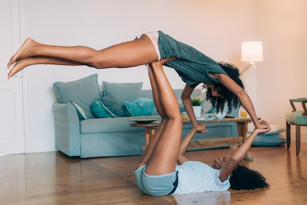 De gelukkige jonge twee zwarte ontspannen thuis het spelen