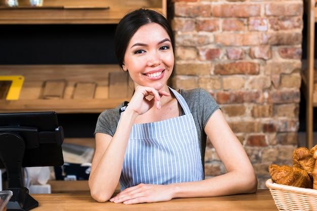 De gelukkige jonge vrouw bij teller bakt binnen winkel bekijkend camera