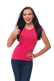 De gelukkige jonge vrouw die duimen toont ondertekent omhoog