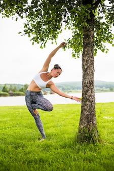 De gelukkige jonge vrouw die zich in yoga bevindt stelt op het gras in het park