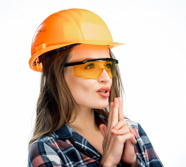 De gelukkige jonge vrouw draagt een oranje veiligheidshelm, een gele bril en een geruit overhemd