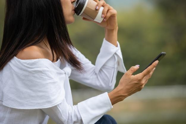 De gelukkige jonge vrouw drinkt koffie en gebruikt smartphone