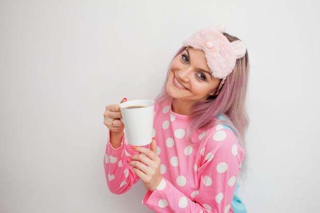 De gelukkige jonge vrouw drinkt ochtendkoffie. mooi meisje in roze pyjama's en slaapmasker