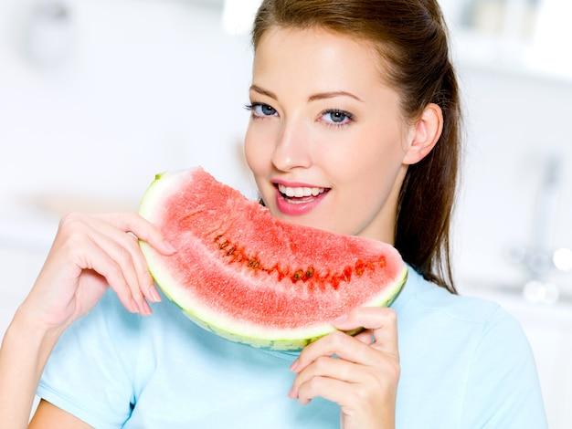 De gelukkige jonge vrouw eet een rode watermeloen