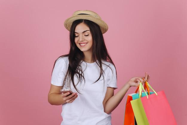 De gelukkige jonge vrouw gebruikt haar telefoon die met kleurrijke het winkelen zakken in de studio stelt