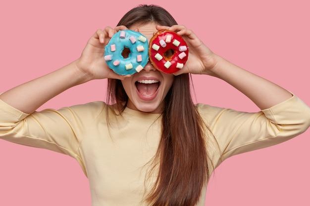De gelukkige jonge vrouw houdt twee smakelijke donuts tegen de ogen, opent de mond van verbazing, geniet van een zoet dessert, geïsoleerd over roze ruimte