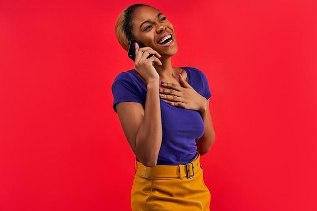De gelukkige jonge vrouw in een blauw t-shirt in een gele rok roept op de telefoon