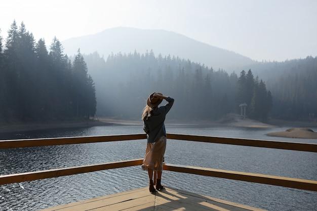 De gelukkige jonge vrouw in hoed geniet van meermening in bergen. ontspannende momenten in het bos. achteraanzicht van stijlvolle meisje geniet van de frisheid buiten. vrijheid, mensen, levensstijl, reizen en vakantie