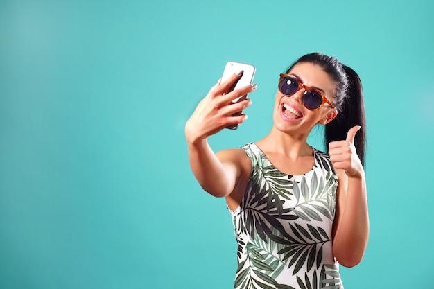 De gelukkige jonge vrouw in zonnebril geeft een duim-omhoog signaal terwijl het stellen in een studio en het nemen van selfies op haar telefoon