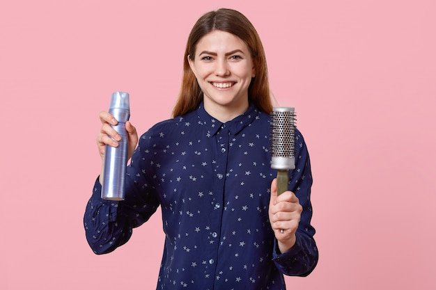 De gelukkige jonge vrouw met donker haar houdt hairspray en kam, gekleed in blauw overhemd, glimlacht breed, geïsoleerd op roze bacground, maakt kapsel. mensen en positiviteitsconcept