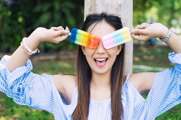 De gelukkige jonge vrouw met kleurrijk roomijs dient binnen tuin in.