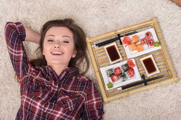 De gelukkige jonge vrouw met sushi ligt thuis op de vloer.