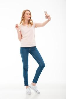 De gelukkige jonge vrouw neemt een selfie door mobiele telefoon.