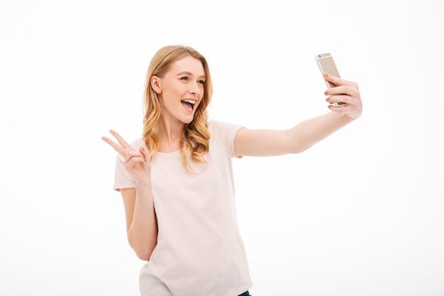 De gelukkige jonge vrouw neemt een selfie met vredesgebaar.