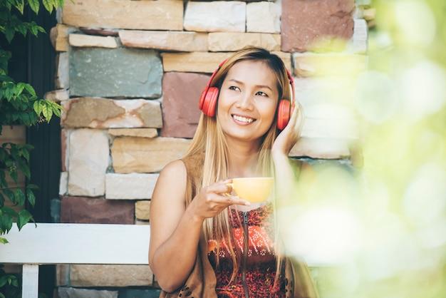 De gelukkige jonge vrouw ontspant met luistert favoriete muziek bij koffie