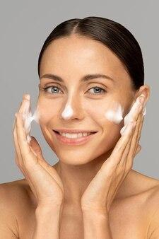 De gelukkige jonge vrouw zorgt voor haar huidgezicht, past reinigingsschuim toe