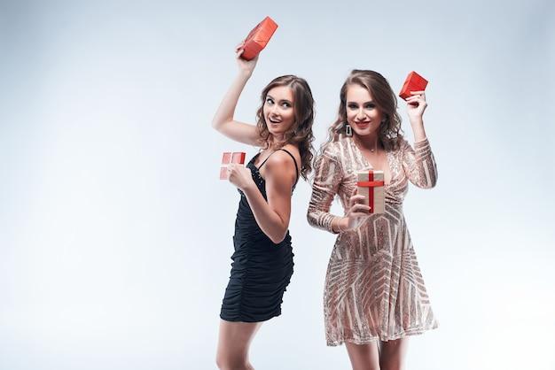 De gelukkige jonge vrouwen die met rood dansen stelt in handen voor die op wit worden geïsoleerd