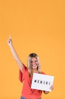 De gelukkige jonge vrouwenholding geniet tekst van tekstvakje met wapen dat voor gele achtergrond wordt opgeheven