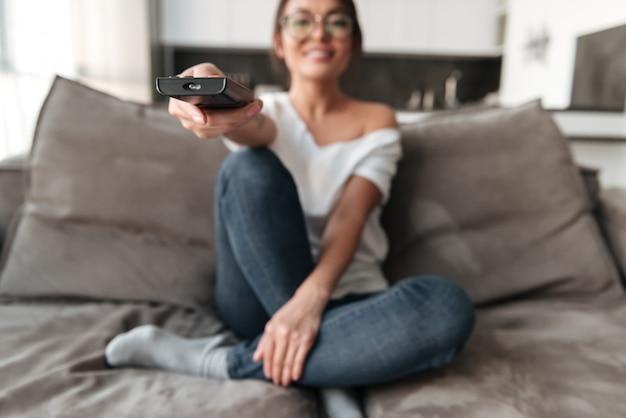 De gelukkige jonge vrouwenzitting op bank kijkt thuis tv.