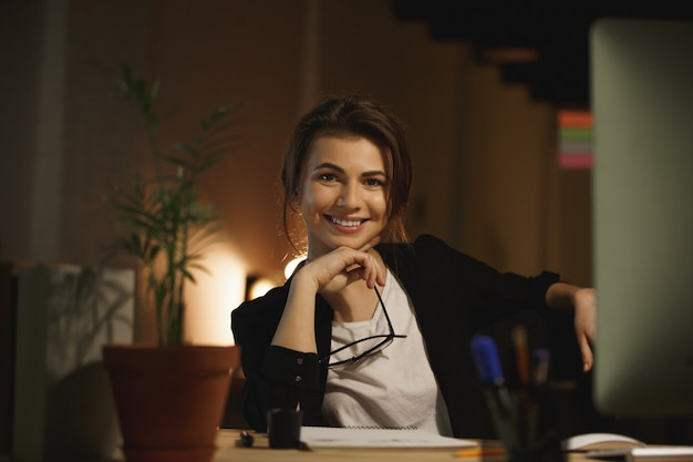 De gelukkige jonge zitting van de vrouwenontwerper in bureau bij nacht