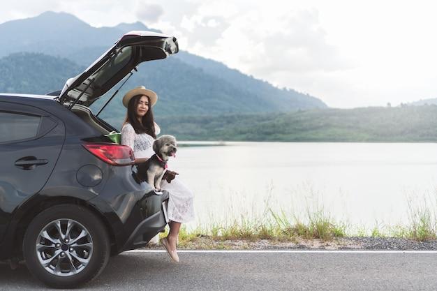 De gelukkige jonge zitting van de vrouwenreiziger in vijfdeursautoauto bij honden bij meer en zonsondergang.