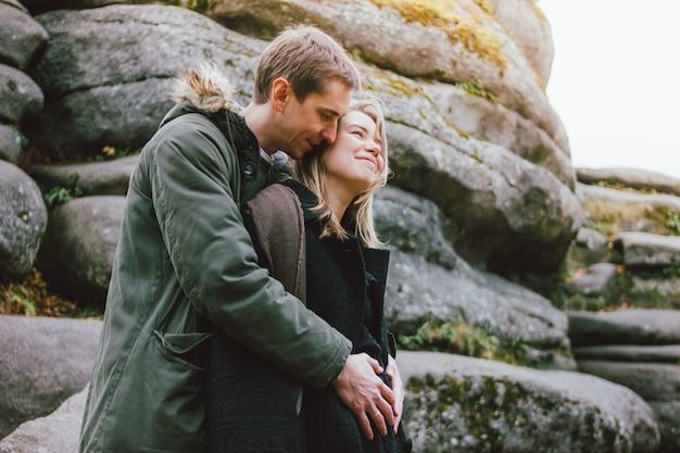 De gelukkige jonge zwangere familie kleedde zich in toevallige stijl die samen op aardpark lopen in koud seizoen, de reis van familieavvenure
