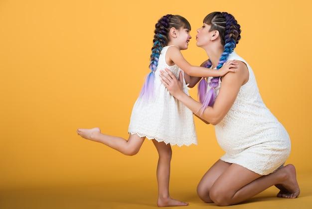 De gelukkige jonge zwangere moeder houdt dochter