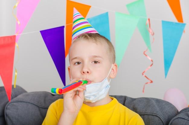 De gelukkige jongen deed zijn gezichtsmasker af en blaast in feestelijke pijp