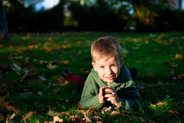 De gelukkige jongen geniet de herfst van park dat pretglimlach heeft