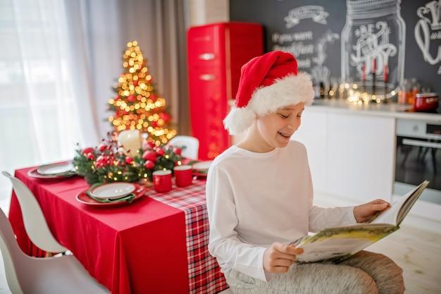 De gelukkige jongen in de hoed van de kerstman viert kerstmis