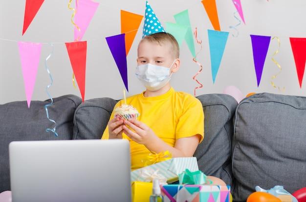 De gelukkige jongen in het gezichtsmasker van de geneeskunde viert verjaardag door videogesprek aan laptop
