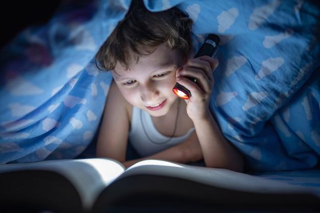 De gelukkige jongen ligt onder deken en leest boek met flitslicht, bij nacht
