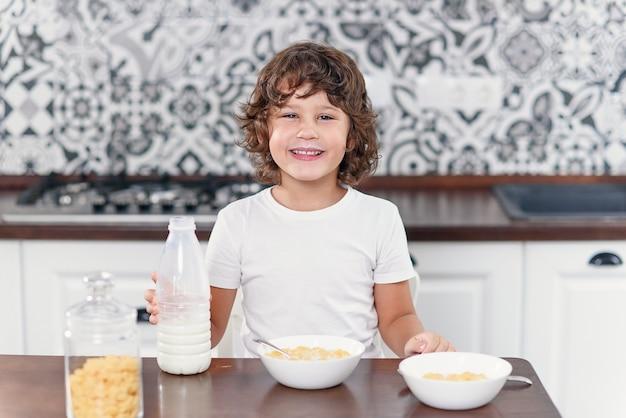 De gelukkige jongen voelt geluk terwijl het eten van gezond ontbijt van cornflakes en melk in de keuken.