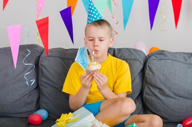 De gelukkige jongen zette zijn gezichtsmasker af, hield vakantie cupcake en blaast kaars uit