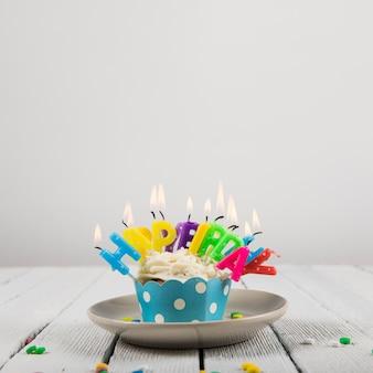 De gelukkige kaarsen van de verjaardagsbrief over de cupcake op ceramische plaat tegen witte achtergrond