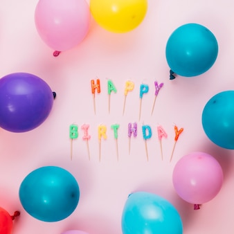De gelukkige kaarsen van de verjaardagstekst met stok en ballons op roze achtergrond