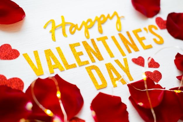 De gelukkige kaart van de de tekstgroet van de valentijnskaartendag met rode roze bloemblaadjes en heartson witte houten achtergrond. romantisch en liefdeconcept